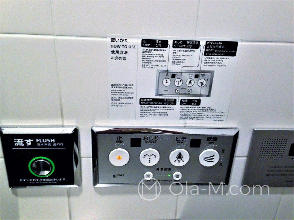 Bajerancka japońska toaleta z instrukcją obsługi, po prawej głośniczek do emitowania dźwięków spłuczki