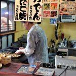 """Kuchnia japońska - takoyaki - kucharz przygotowuje je na specjalnej żeliwnej """"gofrownicy"""" z kulistymi wgłębieniami"""